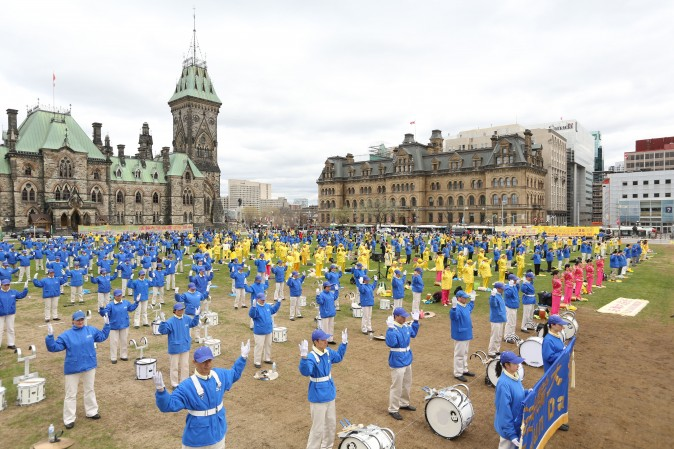 Falun Gong practitioners perform the slow-moving Falun Gong exercises during a celebration on Parliament Hill marking the 25th anniversary of the practice's introduction to the public, May 9, 2017. (Evan Ning/Epoch Times)