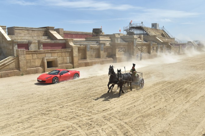 Driver Fabio Barone and his Ferrari 458 Italia competes against a Roman chariot drawn by two horses on 'Ben Hur' movie set at Cinecitta World amusement park in Castel Romano, Italy, on May 11, 2017 (ANDREAS SOLARO/AFP/Getty Images)