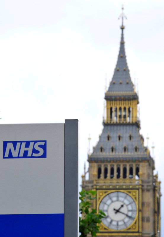 A National Health Service (NHS) sign is seen in the grounds of St Thomas' Hospital, in front of the Houses of Parliament in London on June 7, 2011. (REUTERS/Toby Melville)