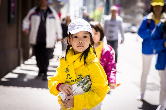 A little child passes out information about Falun Gong during a parade on World Falun Dafa Day in New York on May 12, 2017. (Samira Bouaou/The Epoch Times)