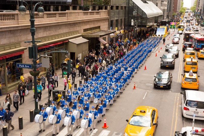 The Divine Land Marching Band marches in a parade along 42nd Street in New York for World Falun Dafa Day on May 12, 2017. (Evan Ningn/The Epoch Times)