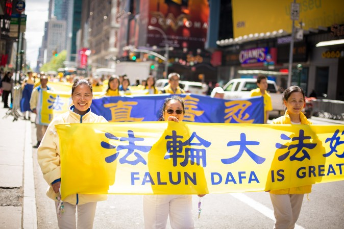 Thousands of Falun Gong practitioners from around the world march in a parade along 42nd Street in New York for World Falun Dafa Day on May 12, 2017. (Benjamin Chasteen/The Epoch Times)