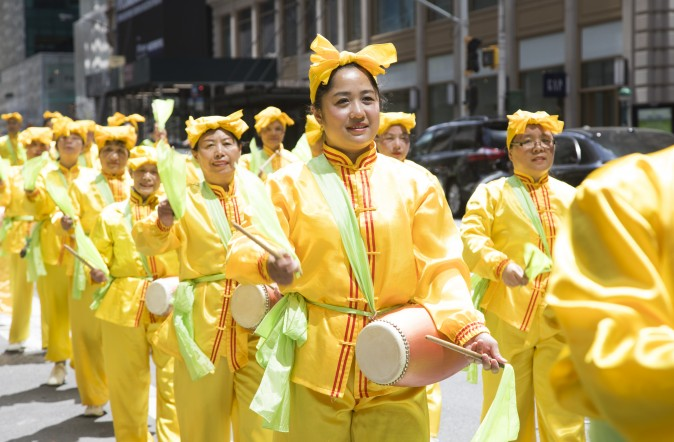 Thousands of Falun Gong practitioners march in a parade along 42nd Street in New York for World Falun Dafa Day on May 12, 2017. (Gary Wong/The Epoch Times)