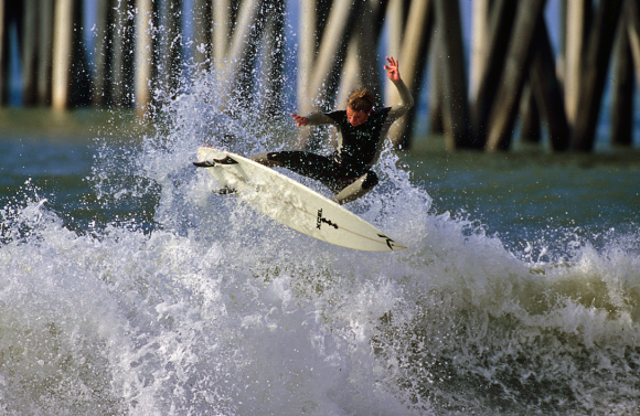 A surfer catches a wave near the pier. (Courtesy of Visit Huntington Beach)