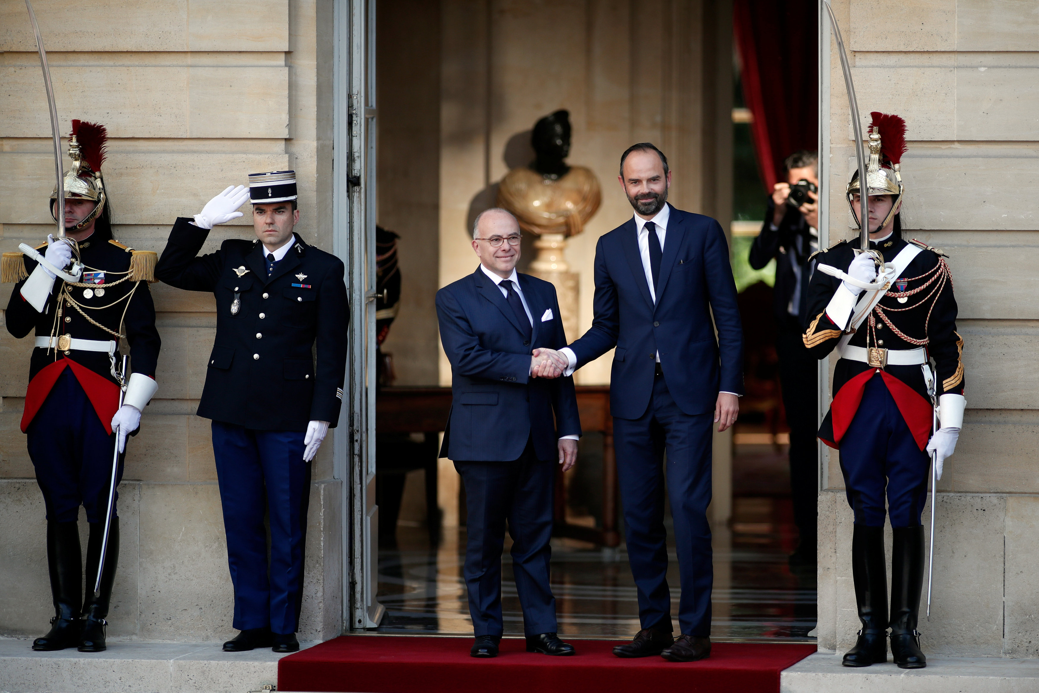 Newly-appointed French Prime Minister Edouard Philippe (R) is greeted by his predecessor Bernard Cazeneuve (L) during a handover ceremony at the Hotel Matignon, in Paris, France on May 15, 2017. ( REUTERS/Benoit Tessier)