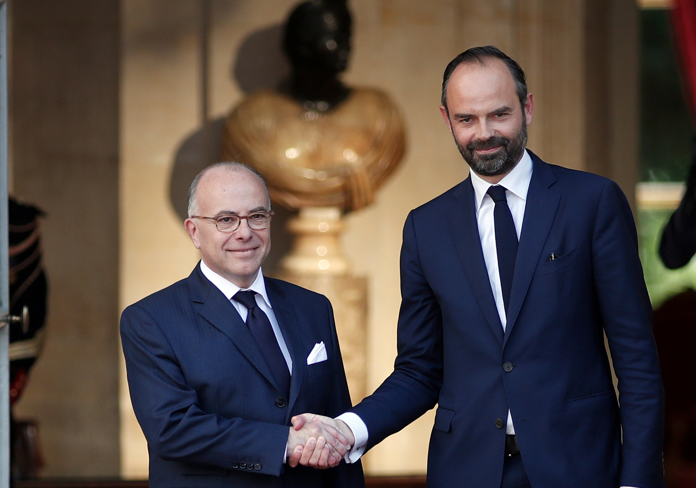 Newly-appointed French Prime Minister Edouard Philippe (R) is greeted by his predecessor Bernard Cazeneuve (L) during a handover ceremony at the Hotel Matignon, in Paris, France on May 15, 2017. (REUTERS/Benoit Tessier)