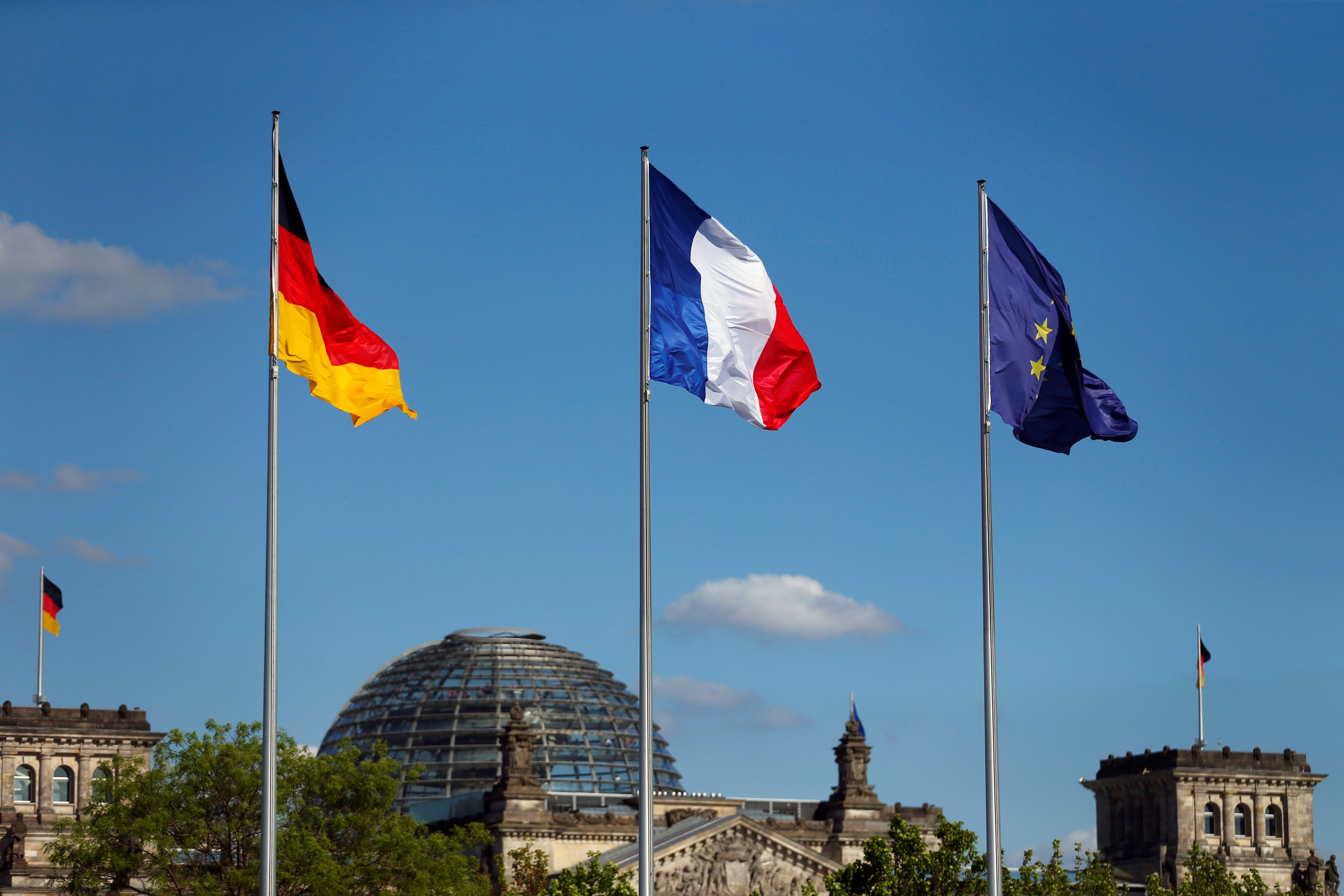 The flags of Germany, France and the European Union are seen in front of the the Chancellery, before the meeting between German Chancellor Angela Merkel and French President Emmanuel Macron in Berlin, Germany on May 15, 2017. (REUTERS/Hannibal Hanschke)