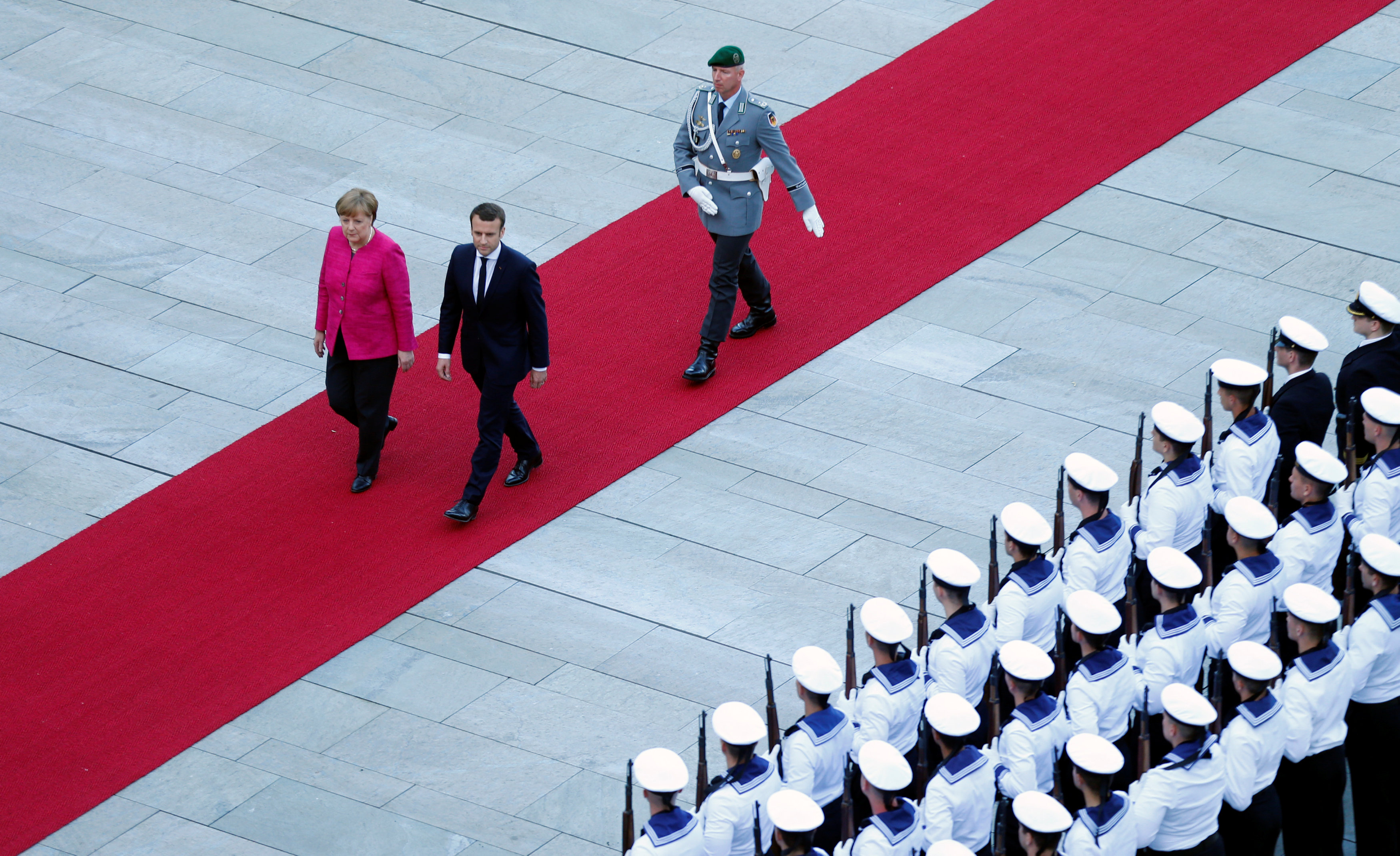 German Chancellor Angela Merkel and French President Emmanuel Macron arrive at a ceremony at the Chancellery in Berlin, Germany on May 15, 2017.   (REUTERS/Hannibal Hanschke)