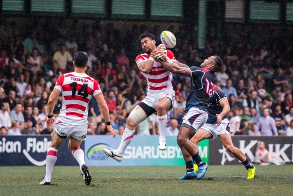 The Japanese winger and try scorer Amanaki Lotoahea jumps for the ball under pressure from Hong Kong centre Lex Kaleca. (Dan Marchant)