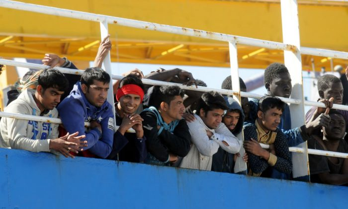 """Men wait on the deck of merchant ship """"Tuna 1"""", at their arrival along with 470 migrants and refugees in the port of Palermo after being rescued at sea off the Libyan coasts, on April 18, 2017. (ALESSANDRO FUCARINI/AFP/Getty Images)"""