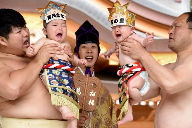 Sumo wrestlers hold up crying babies in front of a referee (C) during a 'Baby-cry Sumo' event in Kanagawa prefecture, Japan, on May 14, 2017. Some 150 babies aged under two, took part in the annual baby crying contest in the Shinto shrine in Sagamihara. Japanese parents believe that sumo wrestlers can help make babies cry out a wish to grow up in good health. (TORU YAMANAKA/AFP/Getty Images)