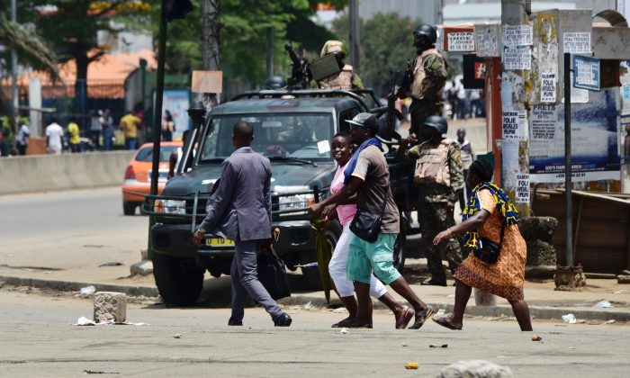 People walk past soldiers of the Republican Guard standing in the street going to the Akouedo's military camp, in Abidjan, Ivory Coast, on May 15, 2017. (Sia Kambou/AFP/Getty Images)