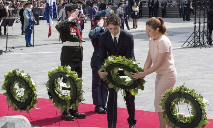 Prime Minister Justin Trudeau and his wife Sophie Gregoire place a wreath in front of a statue of Paul Chomedey de Maisonneuve, the founder of Montreal, during a ceremony marking the 375th anniversary of the founding of the city on May 17, 2017. (The Canadian Press/Paul Chiasson)