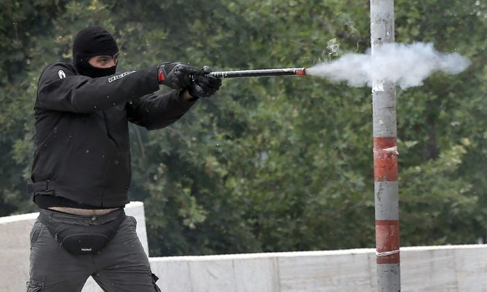 A masked demonstrator fires a projectile at riot police during a 24-hour general strike against the latest round of austerity in Athens, Greece on May 17, 2017. (REUTERS/Alkis Konstantinidis)