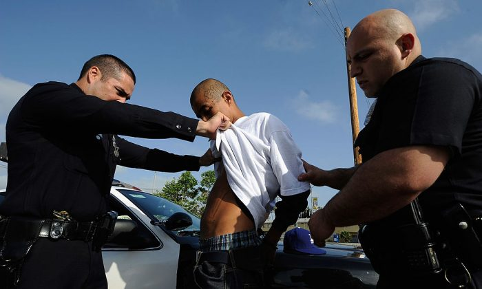 "Los Angeles Police Department officers from the 77th Street division detain a twenty-year old ""Street Villains"" gang member who was recently released from prison  in Los Angeles, Calif., on April 29, 2012. (Kevork Djansezian/Getty Images)"