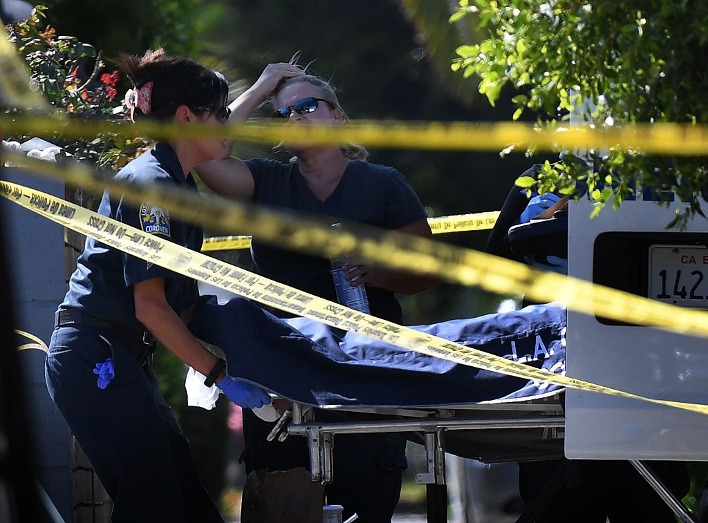 A body is removed by the Los Angeles County coroner staff after three people were killed during a shooting after a dispute at a pop-up Jamaican restaurant in Los Angeles on Oct. 15, 2016. (MARK RALSTON/AFP/Getty Images)