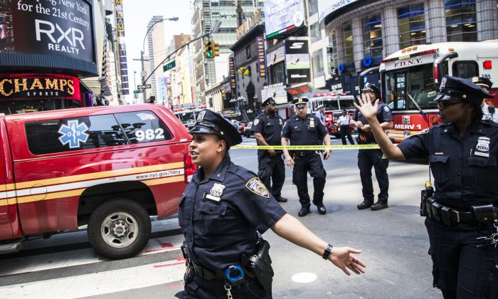 NYPD officers gesture to the crowd to step back after a vehicle struck pedestrians on the sidewalk in Times Square, New York, on May 18, 2017. (Samira Bouaou/The Epoch Times)