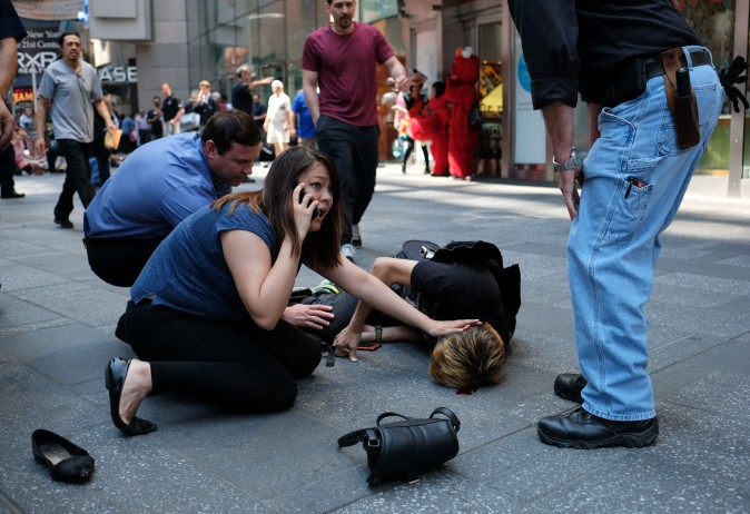 People attend to an injured man after a car plunged into a crowd in Times Square in New York on May 18, 2017. (JEWEL SAMAD/AFP/Getty Images)