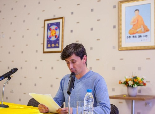 A Falun Dafa practitioner reading his experience sharing paper at the conference. (Minghui.org)