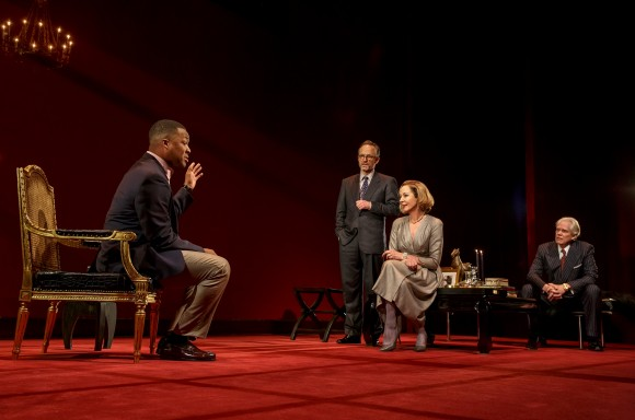 "(L–R) Paul (Corey Hawkins) cons his way into the lives of the affluent couple Ouisa (Allison Janney) and Flan (John Benjamin Hickey) while their friend Geoffrey (Michael Siberry) looks on, from ""Six Degrees of Separation."" (Joan Marcus)"