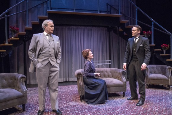 (L–R) Sir James Farringdon (Wynn Harmon), Lady Farringdon (Deanne Lorette) and their son Bob (Ari Brand). The first shows the characters all costumed in shades of gray. (Richard Termine)