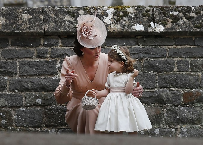 Catherine, Duchess of Cambridge, speaks to her daughter princess Charlotte, a bridesmaid, following the wedding of her sister Pippa Middleton to James Matthews at St Mark's Church in Englefield, west of London, on May 20, 2017. The 33-year-old married financier James Matthews, 41, at a ceremony attended by the royal couple and tennis star Roger Federer. (KIRSTY WIGGLESWORTH/AFP/Getty Images)