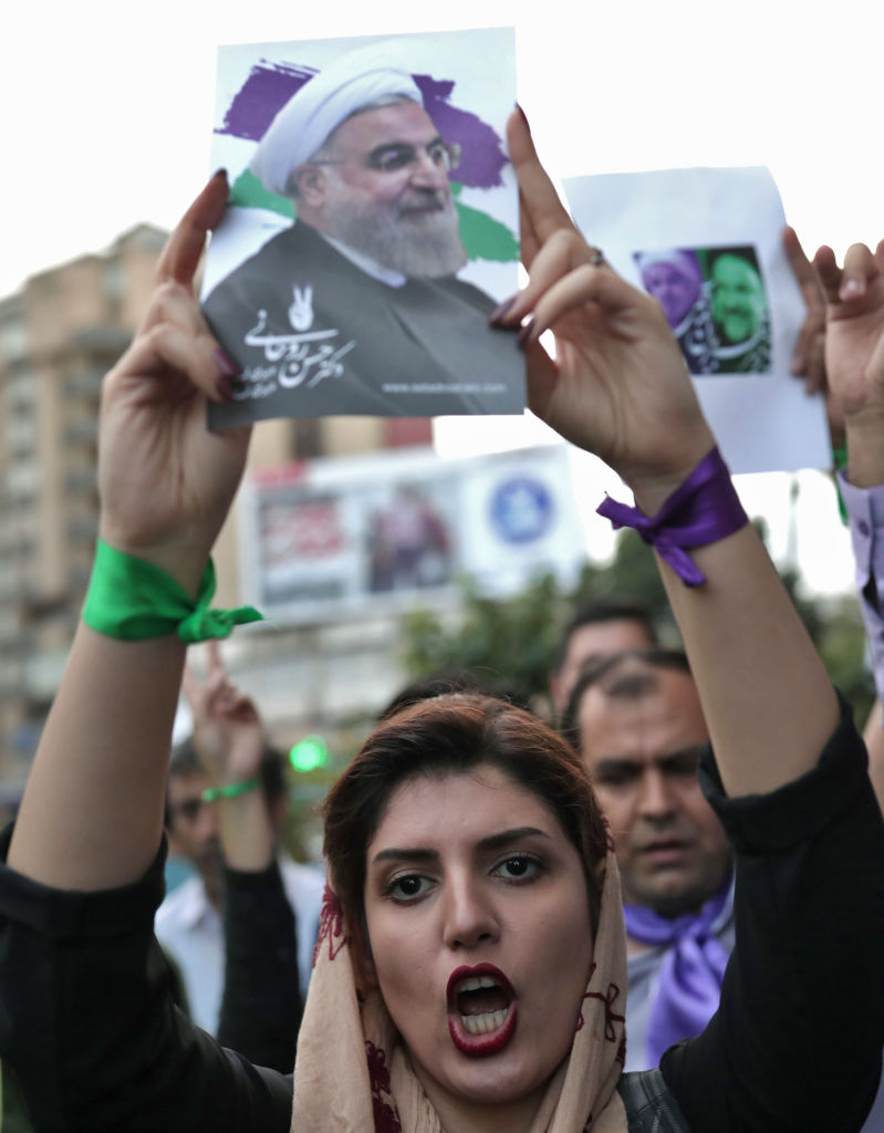 A supporter of newly re-elected Iranian President Hassan Rouhani holds a placard bearing a portrait of him as she takes to the streets to celebrate his victory in downtown Tehran on May 20, 2017.  (BEHROUZ MEHRI/AFP/Getty Images)