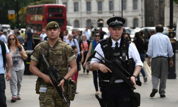 An armed soldier and an armed police officer patrol the streets in London, England on May 24, 2017. (Carl Court/Getty Images)