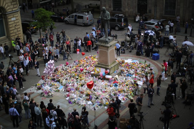 People gather around floral tributes to the victims of the Manchester terror attack ahead of a vigil in St. Ann's Square in Manchester, England, on May 24, 2017. An explosion at Manchester Arena on the night of May 22 at an Ariana Grande concert caused at least 22 fatalities. (Christopher Furlong/Getty Images)
