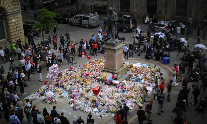 People gather around floral tributes to the victims of the Manchester terror attack ahead of a vigil in St. Ann's Square in Manchester, England, on May 24, 2017. (Christopher Furlong/Getty Images)