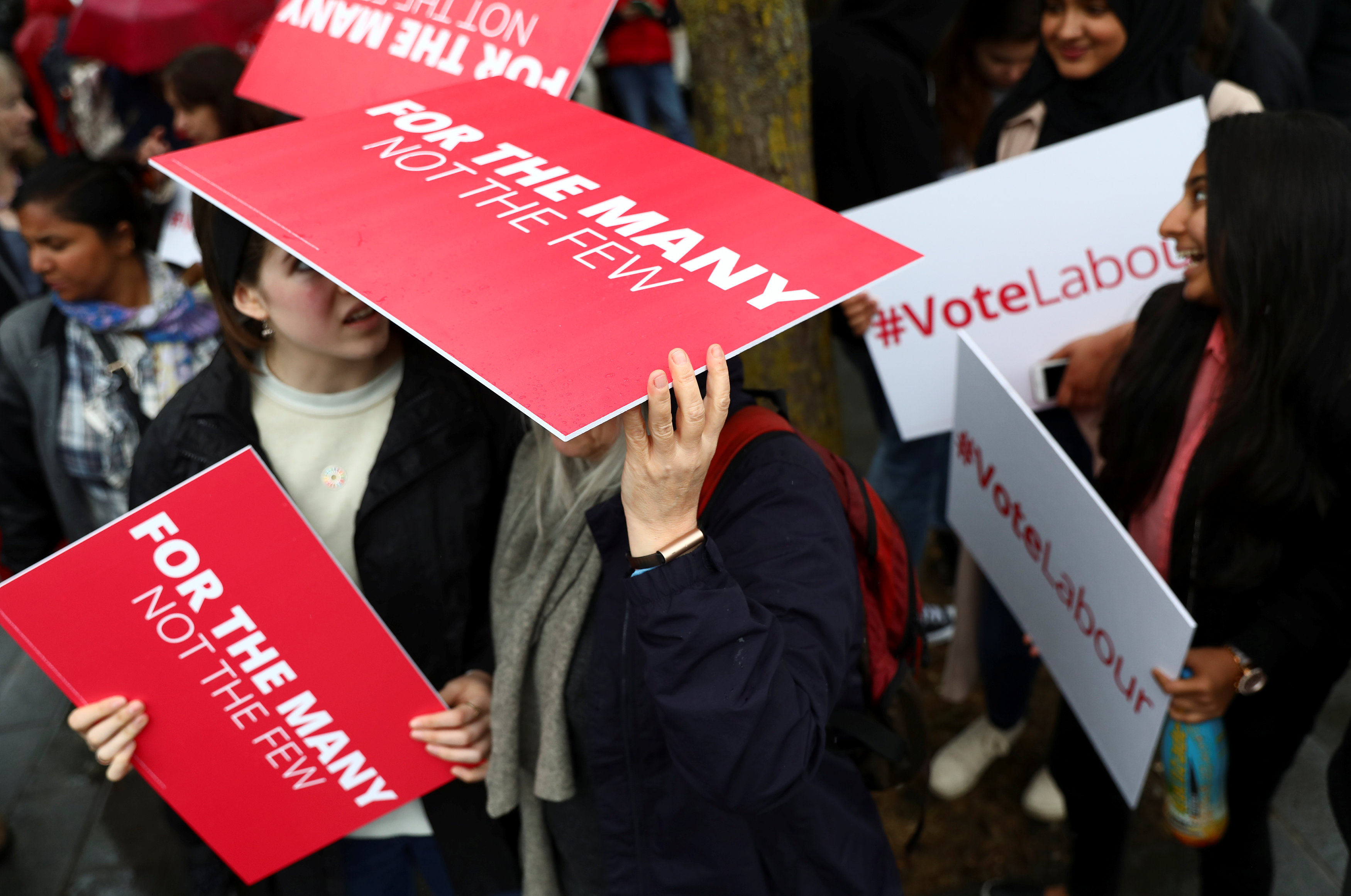 Supporters of Britain's opposition Labour party use placards to shelter from the rain as they campaign in London, Britain on May 18, 2017. (REUTERS/Neil Hall)