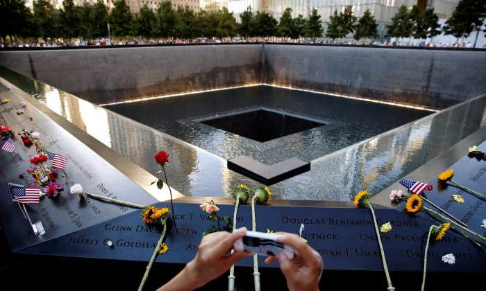 A visitor photographs the National September 11 Memorial and Museum on the 15th anniversary of the 9/11 attacks in Manhattan, New York on Sept. 11, 2016. (REUTERS/Lucas Jackson)