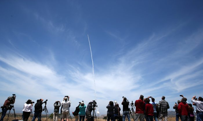 People watch as the Ground-based Midcourse Defense (GMD) element of the U.S. ballistic missile defense system launches during a flight test from Vandenberg Air Force Base, Calif., on May 30, 2017. (Lucy Nicholson/Reuters)