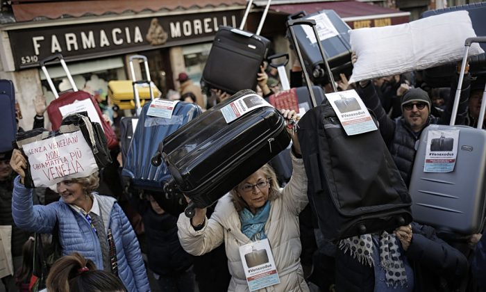 People hold suitcases and signs as they demonstrate against the increasing number of tourists in Venice on Nov. 12, 2016. (MARCO BERTORELLO/AFP/Getty Images)