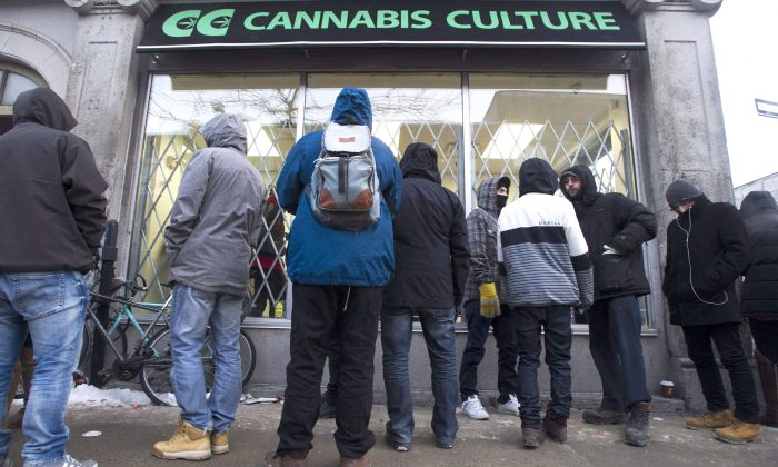 People queue outside Cannabis Culture in Montreal on Dec. 16, 2016. An editorial in the Canadian Medical Association Journal says setting 18 as the benchmark minimum age for buying pot in the government's plan to legalize marijuana is too low. (The Canadian Press/Graham Hughes)