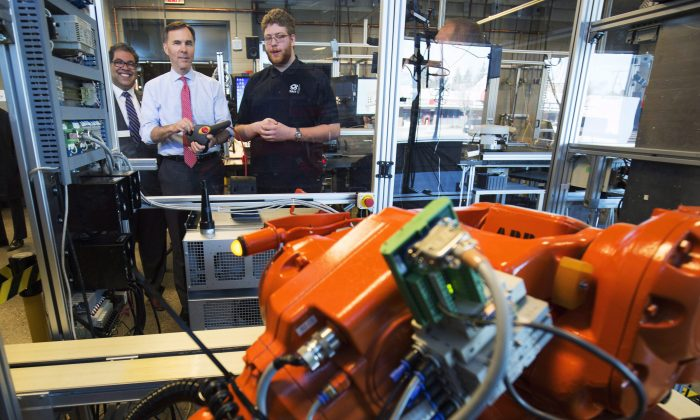 Canada's Minister of Finance Bill Morneau (C) operates a robot with student Spencer Pelzer (R) while Calgary mayor Naheed Nenshi looks on during their tour of the robotics lab at the Southern Alberta Institute of Technology in Calgary on March 27, 2017. Automation threatens many low-skilled jobs, but Canada has benefited from technological advances in the long term. (The Canadian Press/Todd Korol)