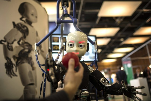 The iCub robot tries to catch a ball during the Innorobo European summit in this 2013 file photo. The event is dedicated to the service robotics industry in Lyon, France. Robots and artificial intelligence threaten low-skilled manufacturing jobs but open opportunities for those capable of creating and programming them. (AP Photo/Laurent Cipriani, File)