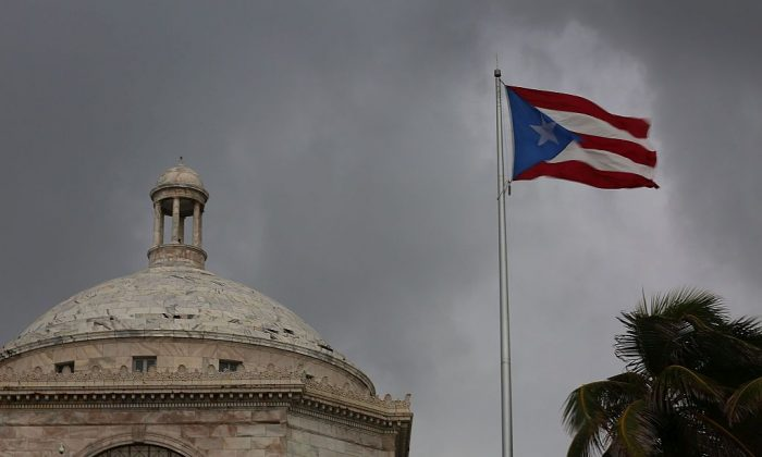 The Puerto Rican flag flies near the Capitol building as the island's residents deal with the government's $72 billion debt  in San Juan, Puerto Rico, on July 1, 2015. (Joe Raedle/Getty Images)