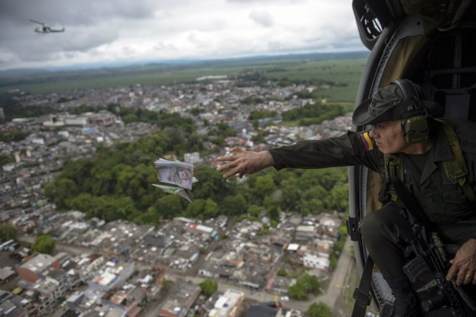 Jose Mendoza, head of Colombia's anti-narcotics police, throws pamphlets offering rewards for information leading to the capture of members of the Gulf Clan cartel, as part of the Agamemnon anti-drug trafficking operation in Apartado, Colombia, on May 31, 2017. (RAUL ARBOLEDA/AFP/Getty Images)