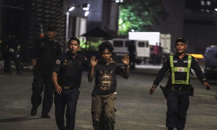 Policemen and a security guard escorting a hotel worker is seen at the entrance of a hotel after a shooting incident inside Resorts World Manila in Pasay City, Metro Manila, Philippines on June 2, 2017. (REUTERS/Stringer)