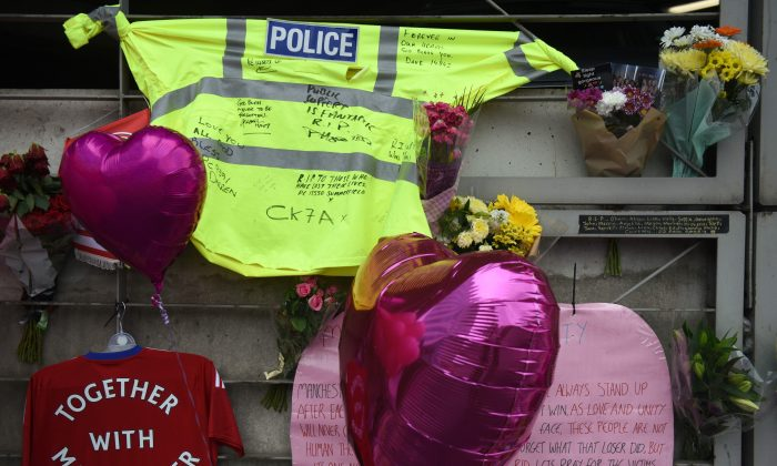 A police officer's hi-vis jacket, adorned with messages of support, is pictured alongside flowers and balloons Victoria Station car park, near to the Manchester Arena in Manchester, northwest England on May 30, 2017, placed in tribute to the victims of the May 22 terror attack at the Manchester Arena. A train station next to the scene of last week's suicide bombing at Manchester Arena, reopened on Tuesday for the first time since the carnage in which 22 people were killed, as the city slowly returned to normal. / AFP PHOTO / Oli SCARFF        (Photo credit should read OLI SCARFF/AFP/Getty Images)