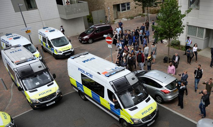 Police vans leave carrying a number of women who were detained after a block of flats was raided in Barking, east London, Britain on June 4, 2017. (REUTERS/Hannah McKay)