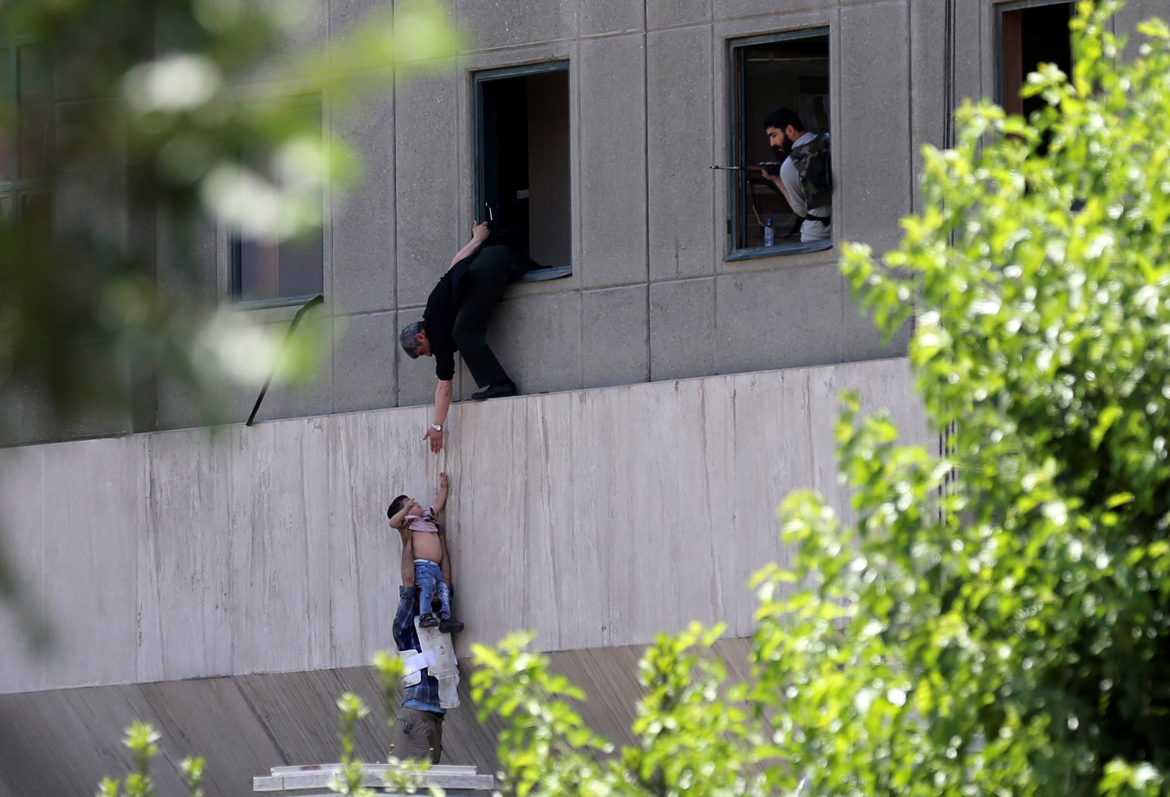 A boy is evacuated during an attack on the Iranian parliament in central Tehran, Iran on June 7, 2017. (Omid Vahabzadeh/TIMA via REUTERS)