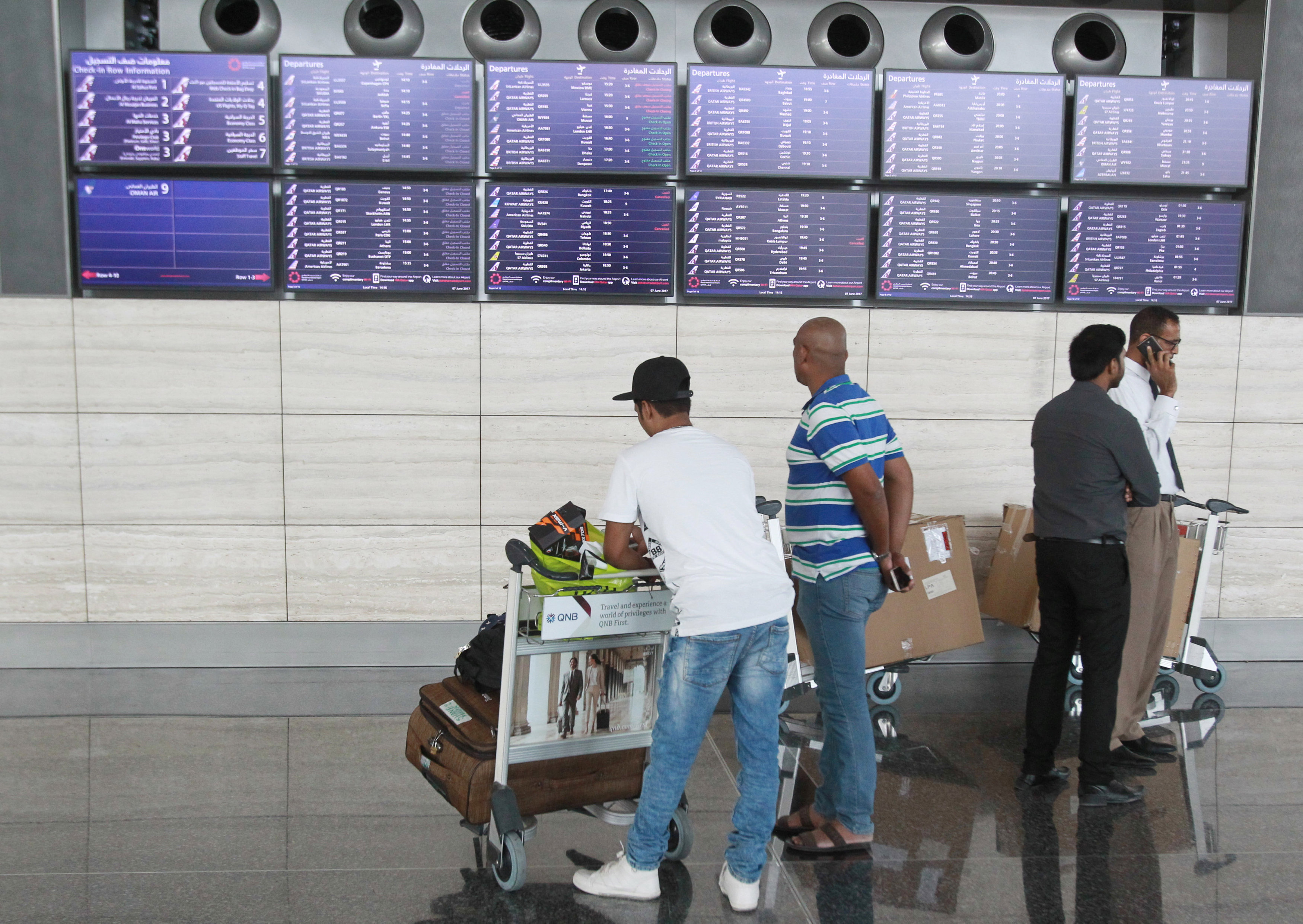 Passengers look at flight details at Hamad International Airport in Doha, Qatar on June 7, 2017. (REUTERS/Naseem Zeitoon)