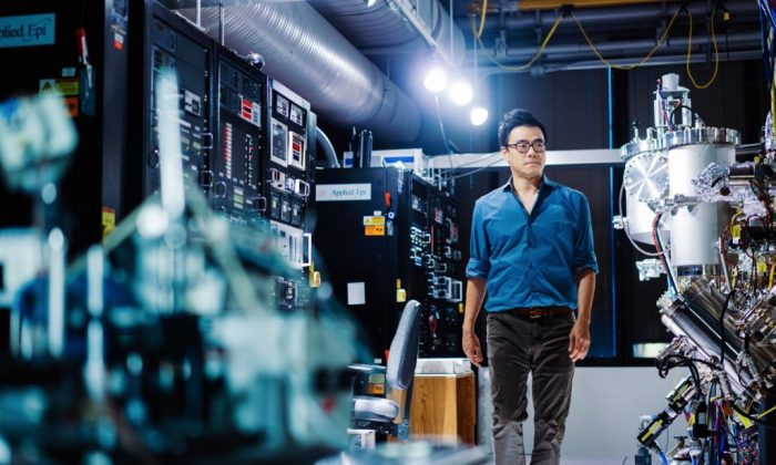 Dr. Jeehwan Kim, a mechanical engineering professor at MIT, with the molecular beam epitaxy system that manufactures semiconductor divices such as the lasers used to read CDs. (Lillie Paquette/MIT School of Engineering)