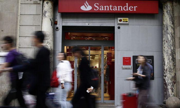 In this file photo, people walk past aBancoSantanderoffice in Barcelona.  (AP Photo/Manu Fernandez)