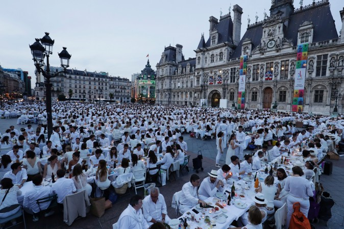 """Participants dressed in white attend a """"Diner en Blanc"""" (Dinner in White) in front of the City Hall in Paris on June 8, 2017. Diner en Blanc, the most chic picnic gathering thousands of participants, takes place every year at a surprise location disclosed at the last minute to the participants. (THOMAS SAMSON/AFP/Getty Images)"""