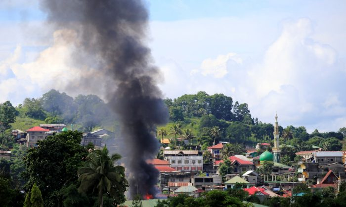 Smoke billowing from a burning building as government troops from the Philippines continue their assault on terrorists from the Maute group, who have taken over large parts of Marawi City. (Reuters/Romeo Ranoco)