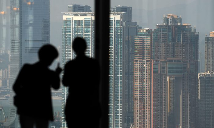 Two people look towards high-rise buildings in Kowloon, Hong Kong, in a file photo. The Hong Kong Monetary Authority and Beijing have agreed to launch a cross-border bond connect, granting foreign investors access to the Chinese onshore bond market. (Antony Dickson/AFP/Getty Images)