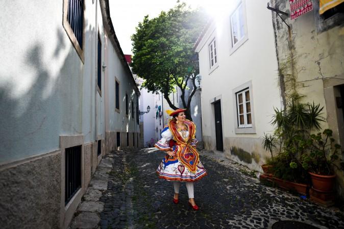 A woman dressed in a traditional costume, walks down a street in the Lisbon neighborhood of Alfama, before attending the Santo Antonio de Lisboa's Parade on Avenida da Liberdade, on June 12. (PATRICIA DE MELO MOREIRA/AFP/Getty Images)